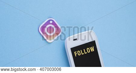 Minsk, Belarus-february 06, 2021: Instagram Icon And Mobile Phone With Word Follow Over Blue Backgro
