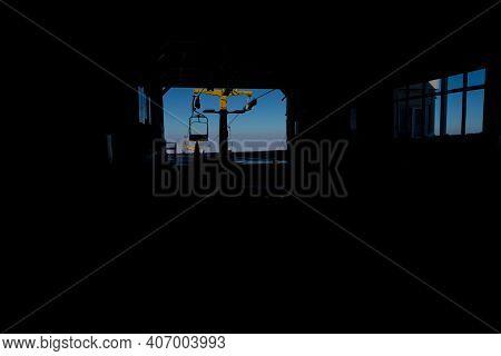 Main Base Of Ski Lift Gondola And Circulating Movement Of Mountain Gondolas In Winter Dark Backgroun