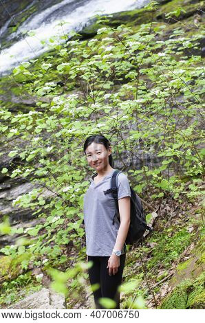 A Smiling Chinese Woman Surrounded By Hobblebush Vibrunum With A Blurred Waterfall Background Outsid