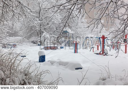 It Is Snowing And Creating Large Drifts. Fresh Snow Cover, Snow-covered Trees And A Playground.
