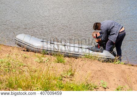 Two Fishermen Install An Outboard Motor On An Inflatable Boat On The River Bank.