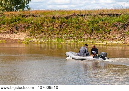 Two Fishermen Float In An Inflatable Boat With An Outboard Motor On A Summer River.
