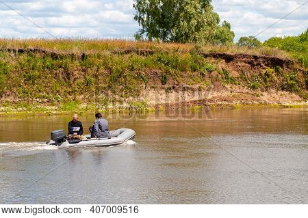 Fishermen Sail In An Inflatable Boat With An Outboard Motor On A Summer River.