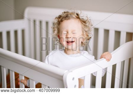 Cute Adorable Baby Boy Crying In Crib At Kids Nursery Room At Home. Funny Baby Boy With Curly Blond