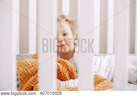 Cute Adorable Baby Boy Toddler Lying In Crib At Kids Nursery Room At Home. Funny Charming Baby Boy W