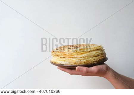 Stack Of Russian Pancake Blini In Rustic Wooden Dish Woman Holds In Hands On A Grey Background. Clos