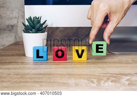 Hand Hold Wooden Cube With Text Love On Table