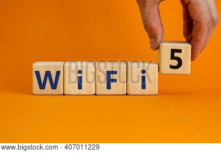Wifi 5 Symbol. Businessman Holds A Wooden Cube With Words Wifi 5. Beautiful Orange Background, Copy