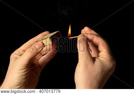 Hands Holds Burning Match On Black Background. A Wooden Match Burns In The Hands Of Macro. Igniting