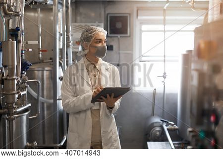 Waist Up Portrait Of Young Woman Wearing Mask And Holding Digital Tablet During Quality Control Insp