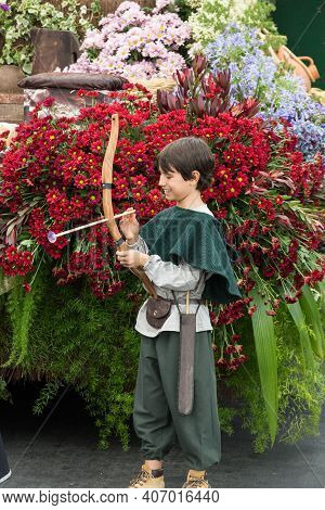 Funchal, Portugal - Sept 4, 2016: A Boy With A Bow And An Arrow In The Background Of A Beautiful Flo