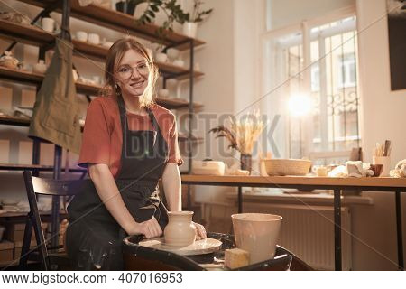 Warm Toned Portrait Of Young Female Artisan Smiling At Camera While Working On Pottery Wheel In Sunl