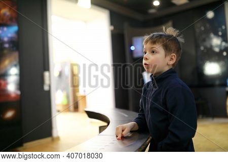 Portrait Of Child Pushing Button In Museum