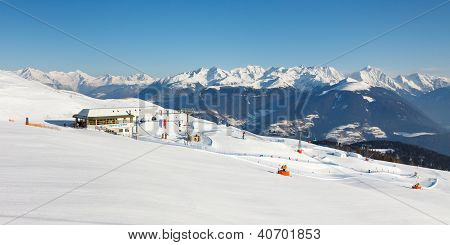 Panoramic view of a ski and countless snow covered mountain peaks in the distance. poster