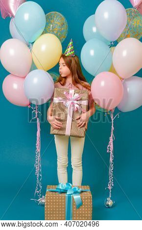 1 White Girl 10 Years Old With A Gift, Pink, Yellow, Blue Balloons For A Holiday On A  Blue Backgrou