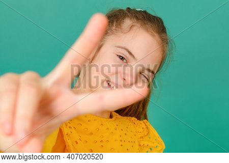 1 White Teenage Girl 10 Years Old In A Yellow Blouse Winks And Shows A Sign Of Peace On A Green Back