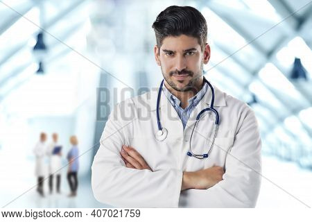Portrait Shot Of Male Doctor Standing With Arms Crossed In The Hospital's Foyer.