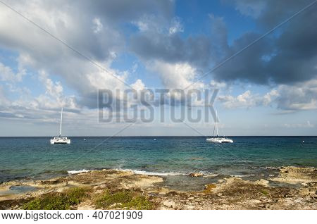 The Morning View Of Two Catamarans Drifting Near The Shore Of Cozumel Island (mexico).