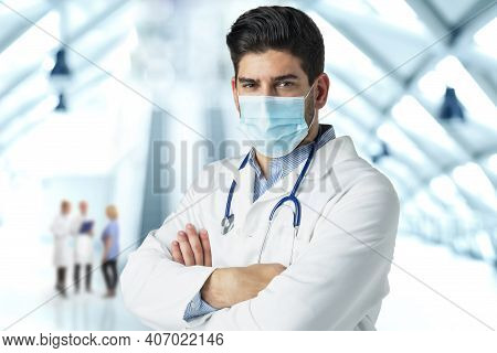 Portrait Of Male Doctor Wearing Surgical Mask While Standing At Hospital's Foyer.