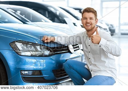 Plus One Driver On The Road! Happy Young Man Showing Thumbs Up Posing Near His Newly Bought Car At T