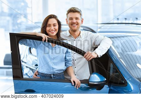 Perfect Family Car. Shot Of A Beautiful Happy Couple Posing Together Behind An Open Door Of A New Ca