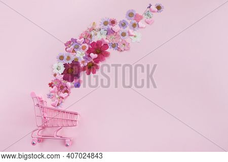Flowers Fly Out Of The Pink Shopping Cart On A Pink Background. Season Sale, Spring Shoping Concept.