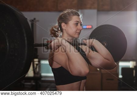 Female Athlete Working Out With Barbell At The Gym. Young Athletic Woman Lifting Barbell. Muscular S