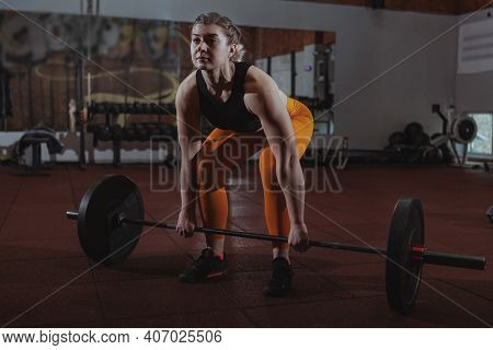 Full Length Shot Of A Strong Female Athlete Working Out With Barbell At The Gym. Focused Sportswoman