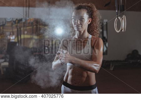 Attractive Female Athlete With Muscular Body Chalking Hands. Beautiful Sportswoman With Perfect Abs