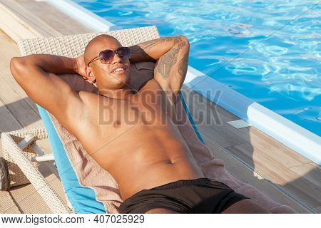 Happy African Athletic Man Relaxing Near The Swimming Pool At Luxury Resort. Attractive Muscular Man