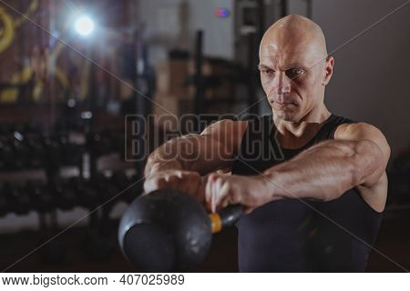 Mature Athletic Man Working Out With Kettlebell At Gym. Concentrated Muscular Sportsman Doing Kettle