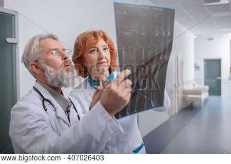Elderly Male And Female Doctors Examining Mri Scan Together. Medical Workers Looking At Mri Scan Of