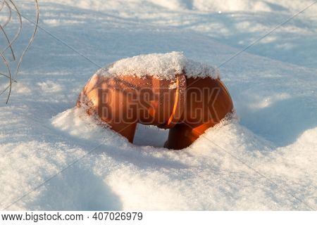 Orange Plumbing Pipe In The Park In Winter.