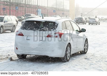 Car In The Parking Lot During The Winter. Snow Is Falling