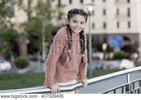 Small Beauty. Small Child With Brunette Hair Plaits Smiling In Casual Fashion Style. Happy Small Gir