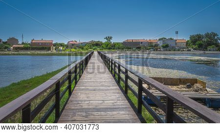 Wooden Bridge Between Fishing Ponds Or Lakes Leading To Residential Suburbs Of Nin With Clear Blue S