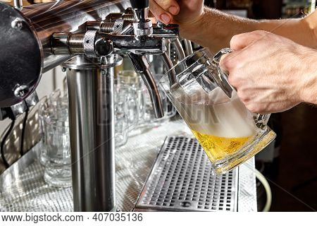 Pouring Beer Into A Mug In A Beer Bar Close-up. Beer Bottling In The Restaurant. The Bar Counter.