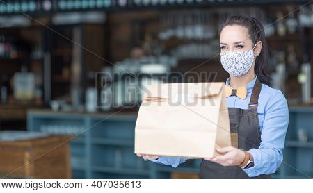 Restaurant Employee Hands Over Food Packed In A Paper Bag Wearing Face Mask During Covid-19 Pandemic