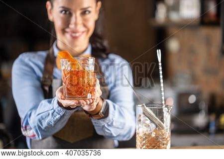 Old Fashioned Drink In Ornamental Glass Offered By A Female Bartender In A Pub.