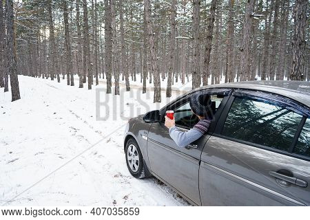 A Young Man Leans Out Of The Car Window And Looks At The Snowy Forest Around. Image Of A White Winte