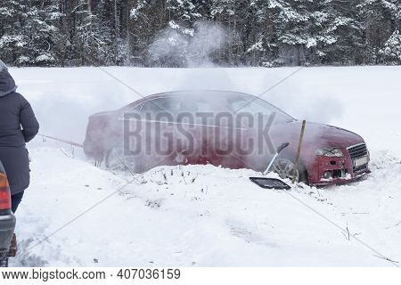 Winter Road. The Red Car Skidded, It Is In A Ditch. Badly Damaged. People Are Trying To Help And Pul