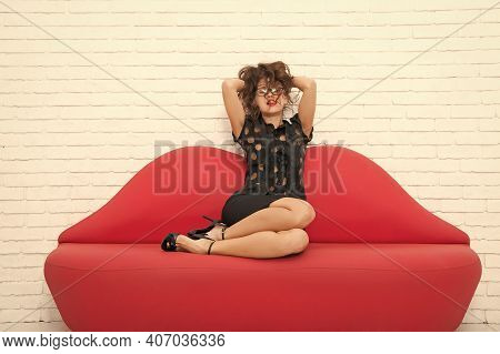 Relaxed Girl Sitting On Red Sofa. Sexy Model On Leather Couch. Beautiful Luxurious Woman Seducing Yo