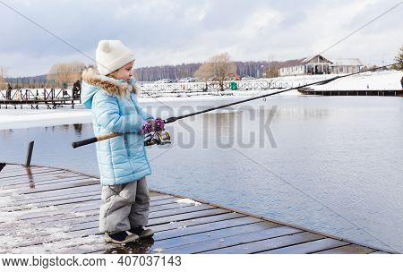 Winter, Spring Fishing On Paid Snow Covered Ice Pond, Lake In Country Club. Little Girl Catching Fis