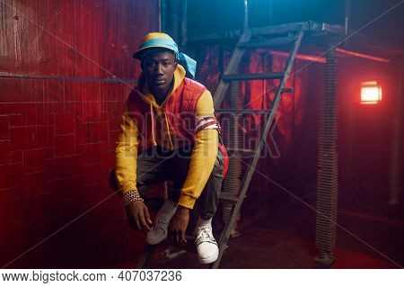 Stylish rapper poses on stairs in grunge studio