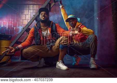Serious rappers with gold jewelry poses in studio