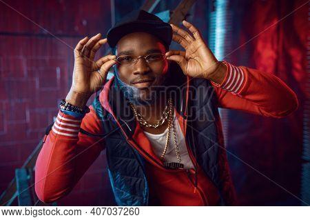 Rapper in stylish gold glasses posing in studio
