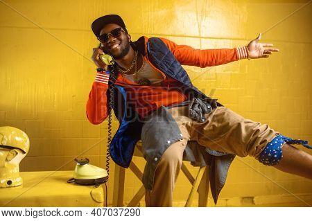 Smiling rapper talking by phone in studio