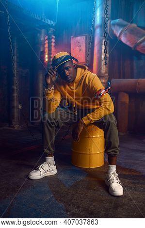 Rapper in yellow hoodie poses in studio
