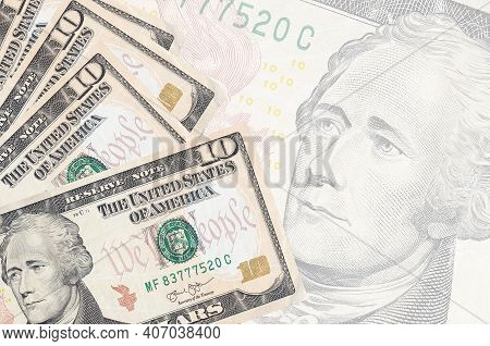 10 Us Dollars Bills Lies In Stack On Background Of Big Semi-transparent Banknote. Abstract Business