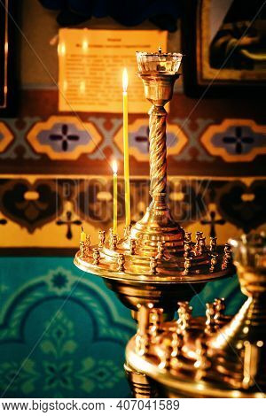 Interior Of An Orthodox Ukrainian Church. Burning Candles On A Gilded Candlestick Or Candelabra